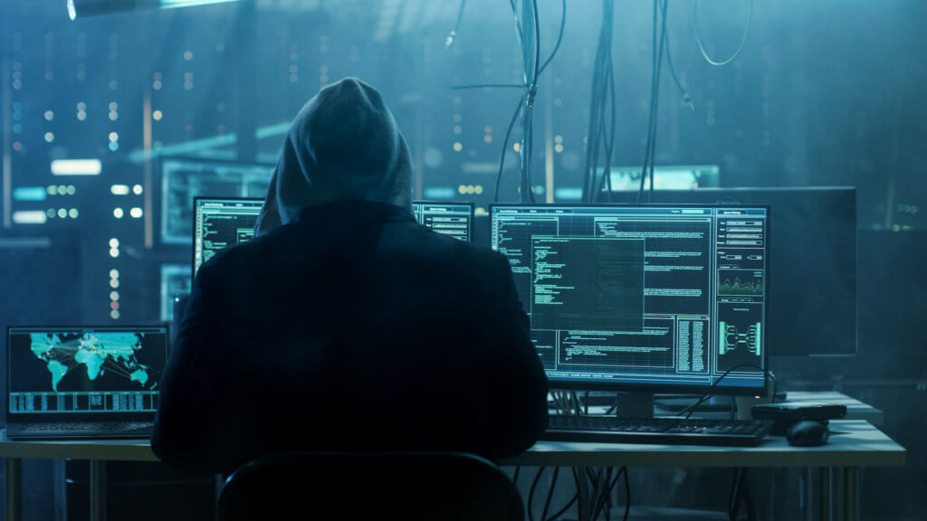 Hooded hacker in front of computer screens