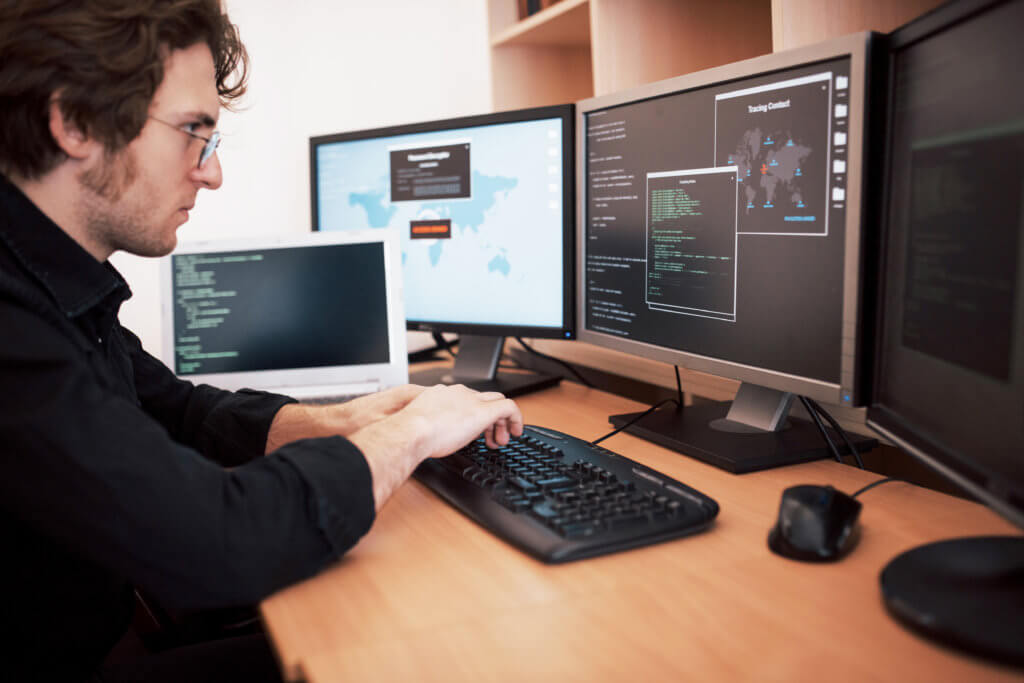 Man in front of several computer screens with code on the screen