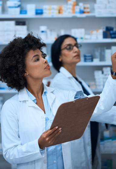 Pharmacist with clipboard checking shelves