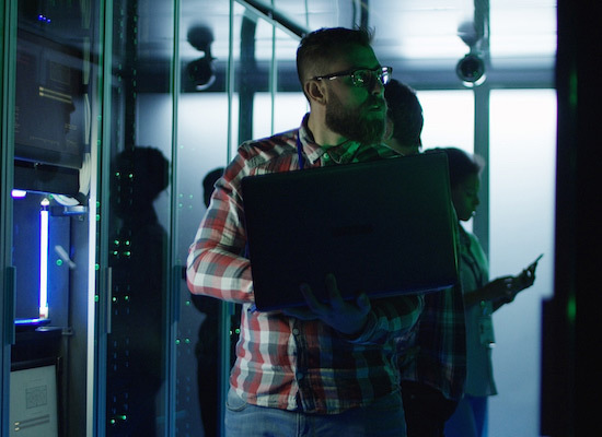 Man holding computer in a server room